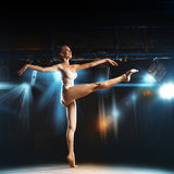Sweet blonde ballerina on stage in theater posing Stock Image