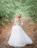 Sweet blonde bride looks over her shoulder. While walking along the path stock photos
