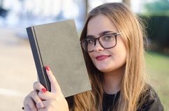 Sweet blonde girl with glasses looking to you and holding a book royalty free stock photography