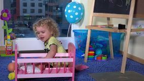 Sweet blonde toddler girl prepare toy bed crib for her baby doll at home stock video