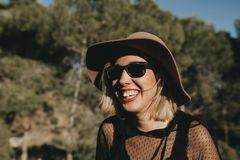 Cool young girl laughing outdoors in nature. Sweet blonde woman with sunglasses and hat laughing in nature at sunset. Close up portrait Stock Photos