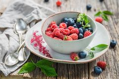 Sweet blueberries and raspberries in white bowl. On old table Stock Image
