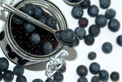 Sweet blueberry jam and a spoon Royalty Free Stock Photos