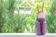 Sweet blueberry milkshake drink. On green nature bokeh at coffee shop Stock Photography