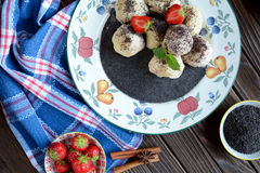 Sweet boiled dumplings filled with strawberries with a poppy seed sauce Stock Image
