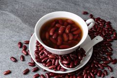 Sweet boiled red beans in white cup on concrete table.  stock photos