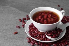 Sweet boiled red beans in white cup on concrete table.  royalty free stock image