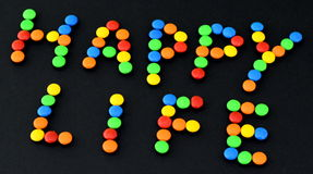 Sweet bonbons with HAPPY LIFE title stock photo