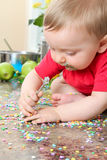 Sweet boy. Cute baby boy eating cake decorations on counter top Royalty Free Stock Photography