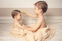 Sweet boy combing little girl in a bed after bath Royalty Free Stock Photos