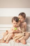 Sweet boy combing little girl in a bed after bath Stock Photography