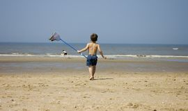 Sweet boy fishing at the beach. Sweet little boy walking towards the ocean with a fishingnet Royalty Free Stock Images