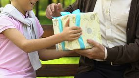 Sweet boy giving Christmas present to his old grandfather, holiday in family stock footage