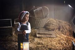 Sweet boy, holding lantern, looking through window, Christmas ti. Me in a barn Royalty Free Stock Image