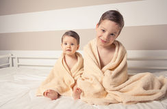 Sweet boy and little girl under towels over a bed Stock Images