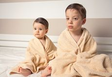 Sweet boy and little girl under towels over a bed Stock Photos
