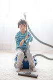 Sweet boy, playing with vacuum cleaner at home Royalty Free Stock Photos