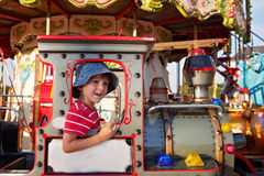 Sweet boy, riding in a train on a merry-go-round, carousel attra Royalty Free Stock Image