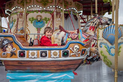 Sweet boy, riding in a train on a merry-go-round, carousel attra Stock Image