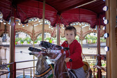 Sweet boy, riding in a train on a merry-go-round, carousel attra Royalty Free Stock Photos