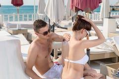 Sweet Boyfriend Applying Lotion on his Girlfriend Royalty Free Stock Photos