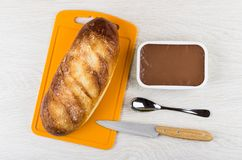 Sweet bread on cutting board, melted chocolate cheese, knife, sp Royalty Free Stock Image