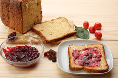 Sweet bread  with raisins and almonds, butter and cherry jam Royalty Free Stock Photo