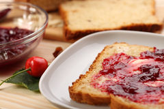 Sweet bread  with raisins and almonds, butter and cherry jam Royalty Free Stock Images