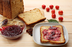 Sweet bread  with raisins and almonds, butter and cherry jam Stock Image