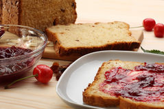 Sweet bread  with raisins and almonds, butter and cherry jam Stock Images