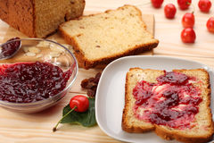 Sweet bread  with raisins and almonds, butter and cherry jam Royalty Free Stock Photography