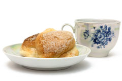 Sweet breakfast. Baked goods on a saucer with a cup of tea isolated on white Stock Photography
