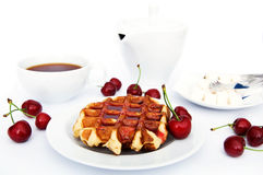 Sweet breakfast. Tasty waffles with jam, tea,  teapot and cherryes over white Stock Photography