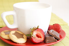 Sweet Breakfast. Sweet meal with cup of milk and cakes and chocolate and strawberries stock photo