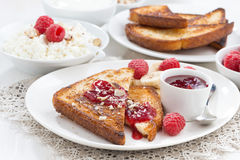 Sweet breakfast - crispy toasts with fresh raspberries, banana. And jam, close-up Stock Photography