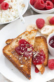 Sweet breakfast - crispy toasts with fresh raspberries, banana. And jam, top view, close-up, vertical Royalty Free Stock Photos