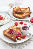 Sweet breakfast - crispy toasts with fresh raspberries, banana. And jam, vertical, top view Royalty Free Stock Photos