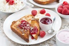 Sweet breakfast - crispy toasts with raspberries, banana and jam Royalty Free Stock Image