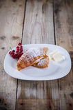 Sweet breakfast. Croissants with berries and butter on a plate Royalty Free Stock Photos
