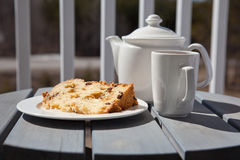 Sweet breakfast - cup of tea with a slice of cake. Tea time - fruit cake served with a cup of tea outside on a sunny morning Stock Photo