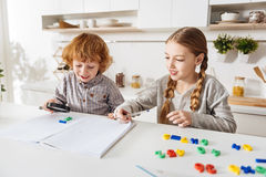 Sweet bright boy helping his sister with homework Royalty Free Stock Photography