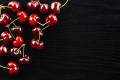 Fresh raw red sweet cherry on black wood. Sweet bright red cherry left upper corner flatlay on black wood stock images