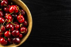 Fresh raw red sweet cherry on black wood. Sweet bright red cherry in a wooden bowl flatlay on black wood royalty free stock photography