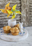 Sweet brioche, Easter ceramic rabbit and homemade paper pinwheel. Easter home baking and Easter decorations. On a light wooden rustic background stock photos