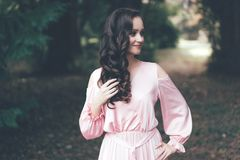 Sweet brunette with curls in a dress royalty free stock photography