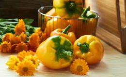 Sweet bulgarian pepper and bunch of orange flowers with tray nearby on wooden table. Sweet bulgarian pepper laying with marigold flowers in front of steel basket stock photography