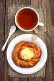 Sweet bun with cream and tea Stock Photo
