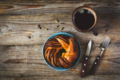 Sweet bun and cup of black coffee on vintage wooden table. Top view, copy space stock images