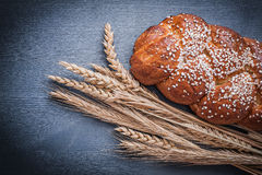 Sweet bun and ears of wheat Royalty Free Stock Photography
