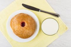 Sweet bun with jam in plate, knife, cup of milk Royalty Free Stock Image